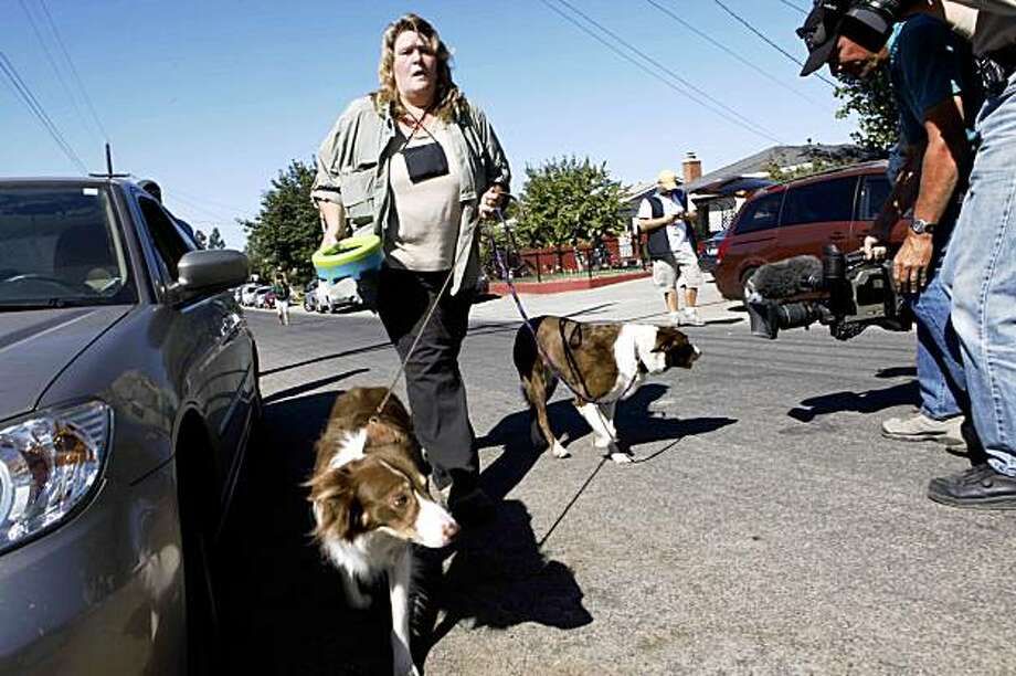 Cadaver dogs from Santa Clara County enter the property on Walnut Avenue after investigators found an unidentified bone fragment on the neighbor's property. Photo: Mike Kepka, The Chronicle