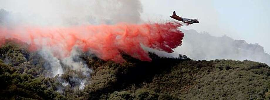 A slurry tanker drops fire retardant on the Oak Glen fire near Yucaipa, Calif., Monday, Aug. 31, 2009. A massive fire in the Angeles National Forest nearly doubled in size overnight, threatening 12,000 homes Monday in a 20-mile (32-kilometer)-long swath of flame and smoke and surging toward a mountaintop broadcasting complex and historic observatory. (AP Photo/Nick Ut) Photo: Nick Ut, AP