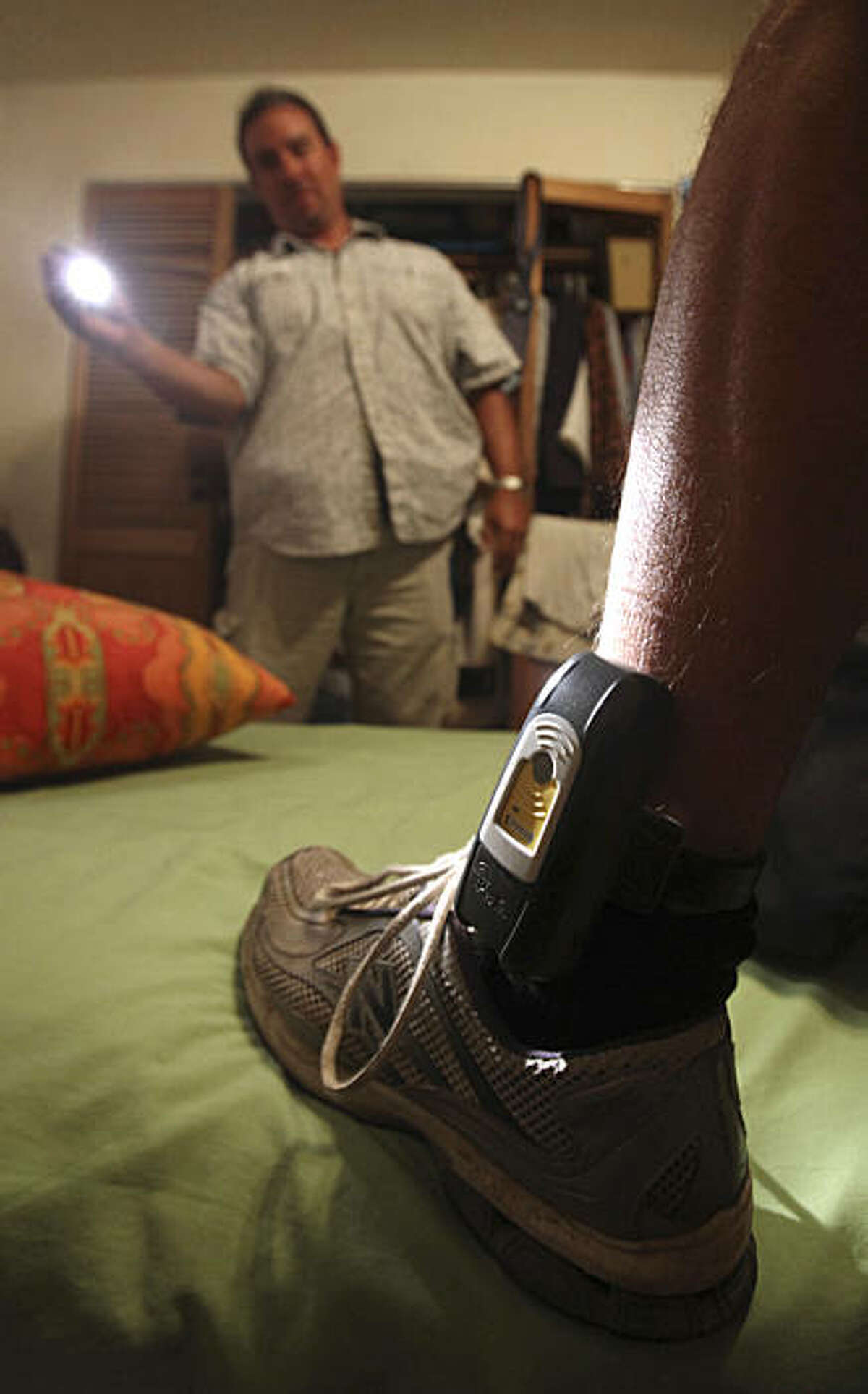 In this photo taken Monday, Aug. 3, 2009, Parole Agent Steve Nakamura uses a flashlight to inspect a GPS locater worn on the ankle of a parolee in Rio Linda, Calif. California lawmakers are expected to vote, Thursday, on a plan by Gov. Arnold Schwarzenegger to change the way the state punishes tens of thousands of criminals. If approved thousands of inmates would be sent to local jails, while others would be released early as a reward for completing prison rehabilitation programs. Electronic monitoring would be expanded to include inmates released to home, hospital or nursing home confinement for ill or infirm inmates, those over age of 60, or any inmate with less than 12 months left to serve. Parole agents can check the location of where individual is or has been.(AP Photo/Rich Pedroncelli)
