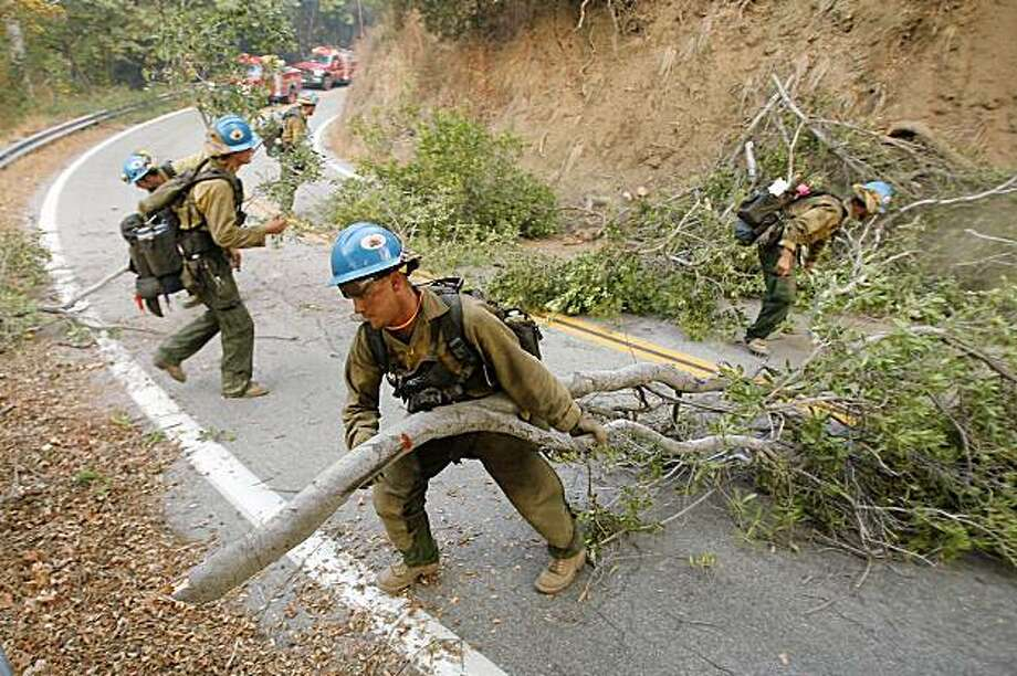 SANTA CLARITA, CA - SEPTEMBER 3:  Firefighters of the Blue Ridge Hotshots crew from the Coconino National Forest in Arizona clear trees and brush along the road and near 15 to 20 homes where mandatory orders were implemented before sunrise as a flare-up on the western front of the 226-square-mile Station Fire threatens to send the fire into the Dillon Divide near Pacoima Canyon on September 3, 2009 near Santa Clarita, California. Two firefighters died when their truck rolled off an 800-foot drop-off as they fled advancing flames and three other people were injured by the fire. Nearly 20 percent of the Angeles National Forest has been charred and 62 homes have been destroyed. The fire is now 38 percent contained, up from 28 percent yesterday. The Station Fire is reportedly the largest in Los Angeles County history.  (Photo by David McNew/Getty Images) Photo: David McNew, Getty Images