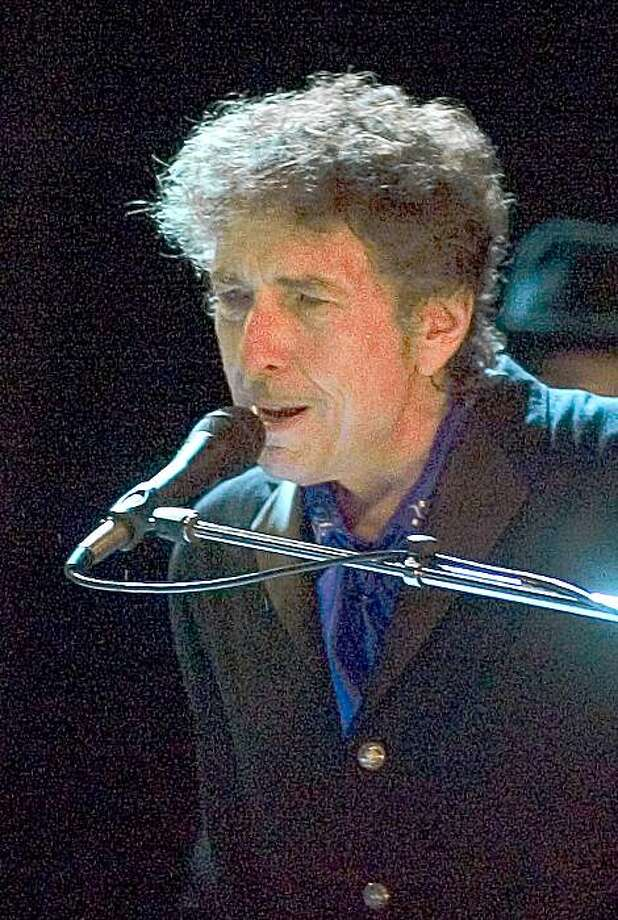 FILE - In this Aug. 26, 2006 file photo, Bob Dylan performs as the opening act of the Pawtucket Arts Festival at McCoy Stadium, in Pawtucket, R.I. Rock legend Bob Dylan was treated like a complete unknown by police in a New Jersey shore community when a resident called to report someone wandering around the neighborhood. Long Branch business administrator Howard Woolley says a 24-year-old police officer apparently was unaware of who Dylan is and asked him for identification.   (AP Photo/Stew Milne, File) Photo: Stew Milne, AP