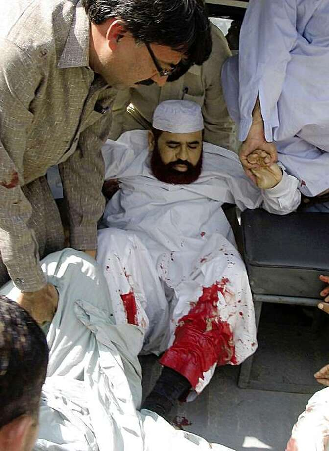Injured Pakistani Religious Affairs Minister Hamid Saeed Kazmi is rushed to a hospital in Islamabad, Pakistan, Wednesday, Sept. 2, 2009. Gunmen opened fire on a vehicle carrying Kazmi, wounding him and killing his driver, police said. (AP Photo) Photo: AP