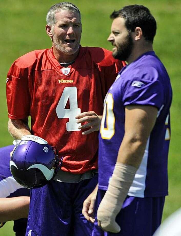 New Minnesota Vikings quarterback Brett Favre (4) talks with teammate Jim Kleinsasser (40) during NFL football training camp, Tuesday, Aug. 18, 2009 in Eden Prairie, Minn. (AP Photo/Hannah Foslien) Photo: Hannah Foslien, AP