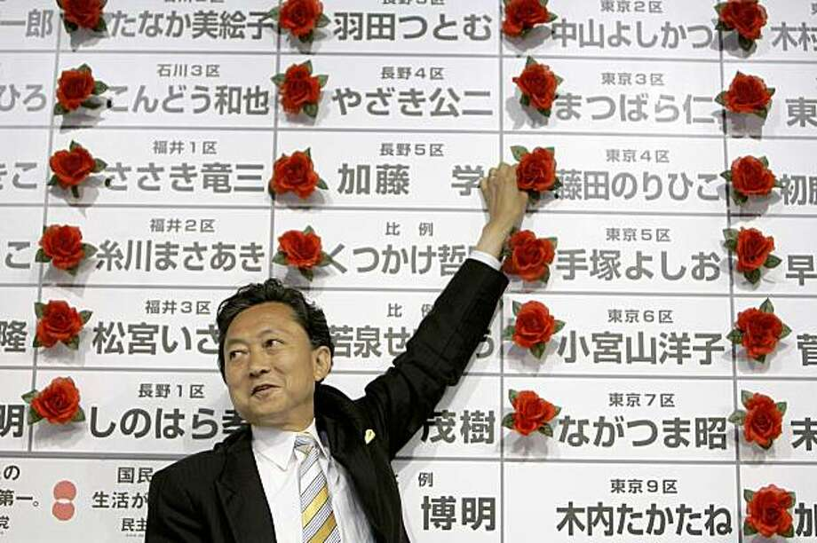 Yukio Hatoyama, leader of Japan's main opposition Democratic Party of Japan, smiles with red rosettes attached on victorious candidates' names during the ballot counting for the parliamentary elections at the party's election center in Tokyo Sunday, Aug. 30, 2009. The DPJ was set to win 300 of the 480 seats in the lower house of parliament, ousting the Liberal Democrats, who have governed Japan for all but 11 months since 1955, according to projections by all major Japanese TV networks. (AP Photo/David Guttenfelder) Photo: David Guttenfelder, AP