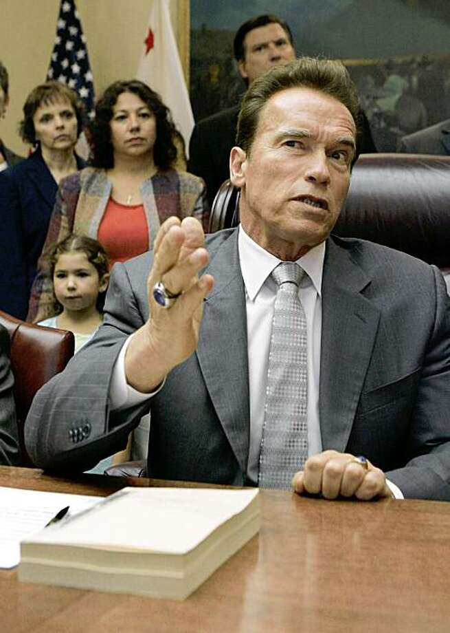 With the signed budget bill in front of him Gov. Arnold Schwarzenegger answers a reporters question concerning the $85 billion revised state budget that he signed during ceremonies at the Capitol in Sacramento, Calif., Tuesday, July 28, 2009. (AP Photo/Rich Pedroncelli) Photo: Rich Pedroncelli, AP