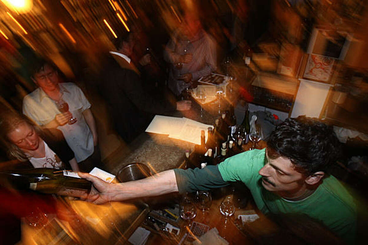 Luc Ertoran (bottom) , Terroir owner, pours wine during a tasting of natural wines at Terroir in San Francisco, Calif. on Monday, August 24, 2009.