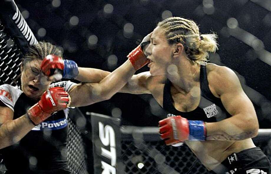 """Cris """"Cyborg"""" Santos, of Brazil, right, trades punches with Gina Carano in a Strikeforce mixed martial arts Female Middleweight Championship match on Saturday, Aug. 15, 2009, in San Jose, Calif. Santos won by TKO in the first round to win the championship. (AP Photo/Jeff Chiu) Photo: Jeff Chiu, AP"""