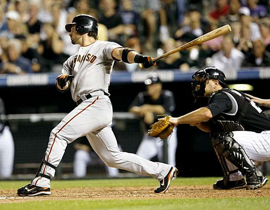 San Francisco Giants' Aaron Rowand, left, hits a three-run home run as Colorado Rockies catcher Chris Iannetta looks on in the fourth inning of a baseball game in Denver on Friday, Aug. 21, 2009. (AP Photo/David Zalubowski) Photo: David Zalubowski, AP