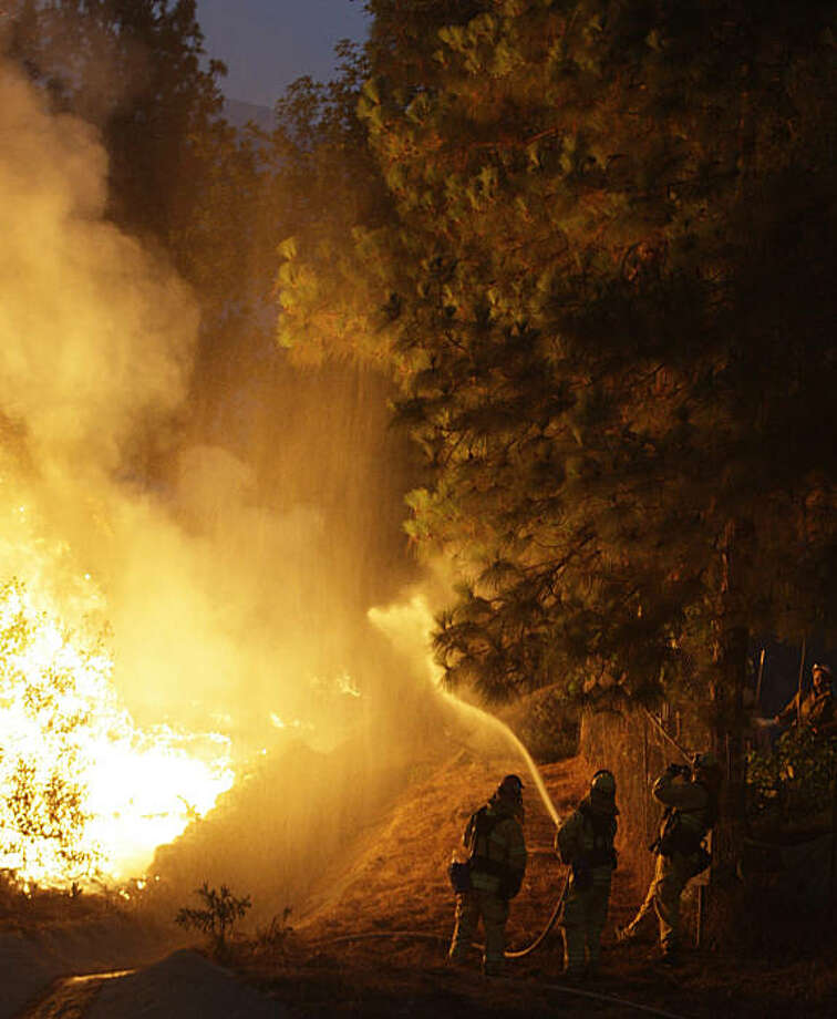 Firefighters work a fire threatening houses in the  La Crescenta section of Glendale, Calif., Tuesday, Sept. 1, 2009. Photo: LM Otero, AP
