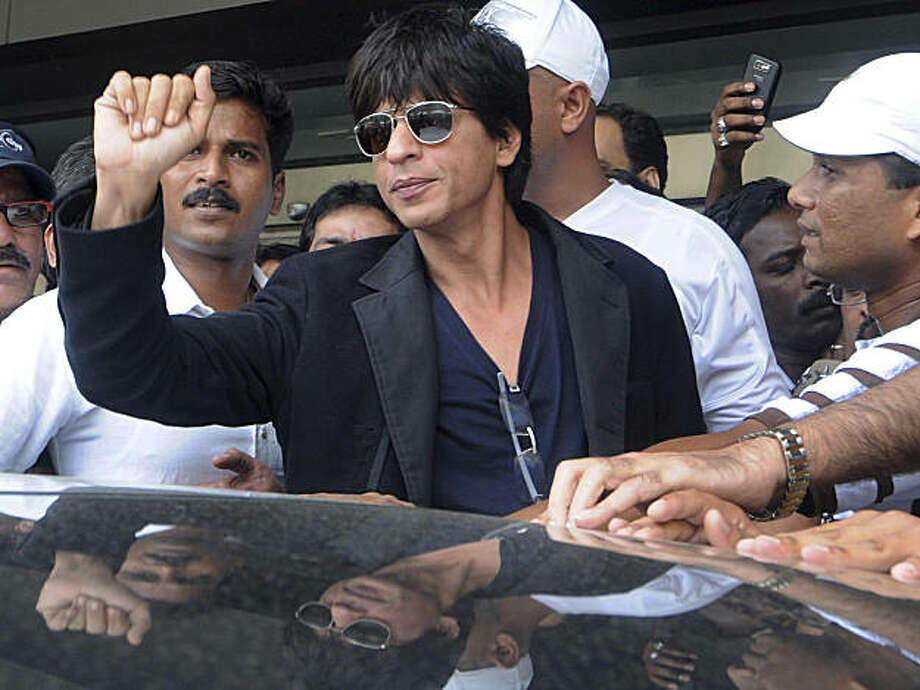 Bollywood actor Shah Rukh Khan, center, gestures upon his arrival at the international airport in Mumbai, India, Tuesday, Aug. 18, 2009. Khan says news of his questioning by U.S. immigration officials has been blown out of proportion. He was questioned at a US airport after his name was triggered in a computer alert. US immigration officials denied he was formally held. (AP Photo) Photo: AP