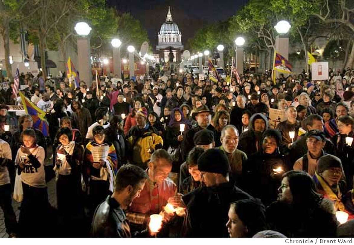 Even before the speakers were finished, the crowd lit their candles near the glow of San Francisco City Hall. Hundreds of supporters including actor Richard Gere and Archbishop Desmond Tutu took part in a candle light vigil near United Nations Plaza in San Francisco Tuesday, April 8, 2008. Photo by Brant Ward / San Francisco Chronicle