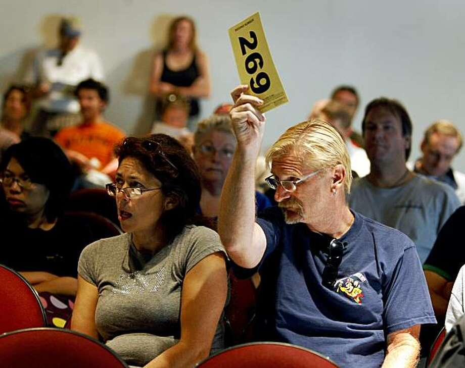 Brian Garnier, sitting with his girlfriend Jeanine DuBois (left), bids on an assortment of food service items at a government auction of surplus equipment hosted by the Presidio Trust in San Francisco, Calif., on Friday, Aug. 28, 2009. Photo: Paul Chinn, The Chronicle