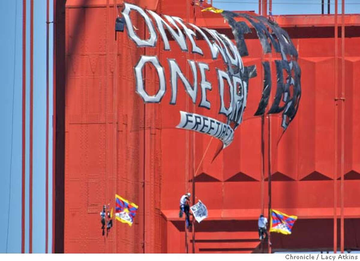 Three protesters climb the Golden Gate Bridge cables unfurl a banner,