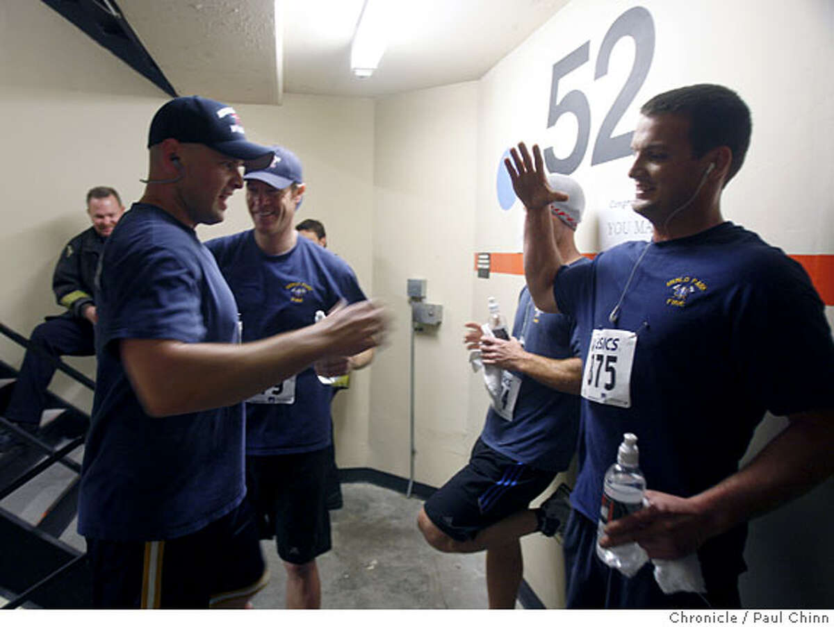 Andrew Murtagh, left, is congratulated by fellow firefighters from the Menlo Park Fire Department after crossing the finish line of the second annual California stair in San Francisco, Calif., on Saturday, March 29, 2008. Photo by Paul Chinn / San Francisco Chronicle