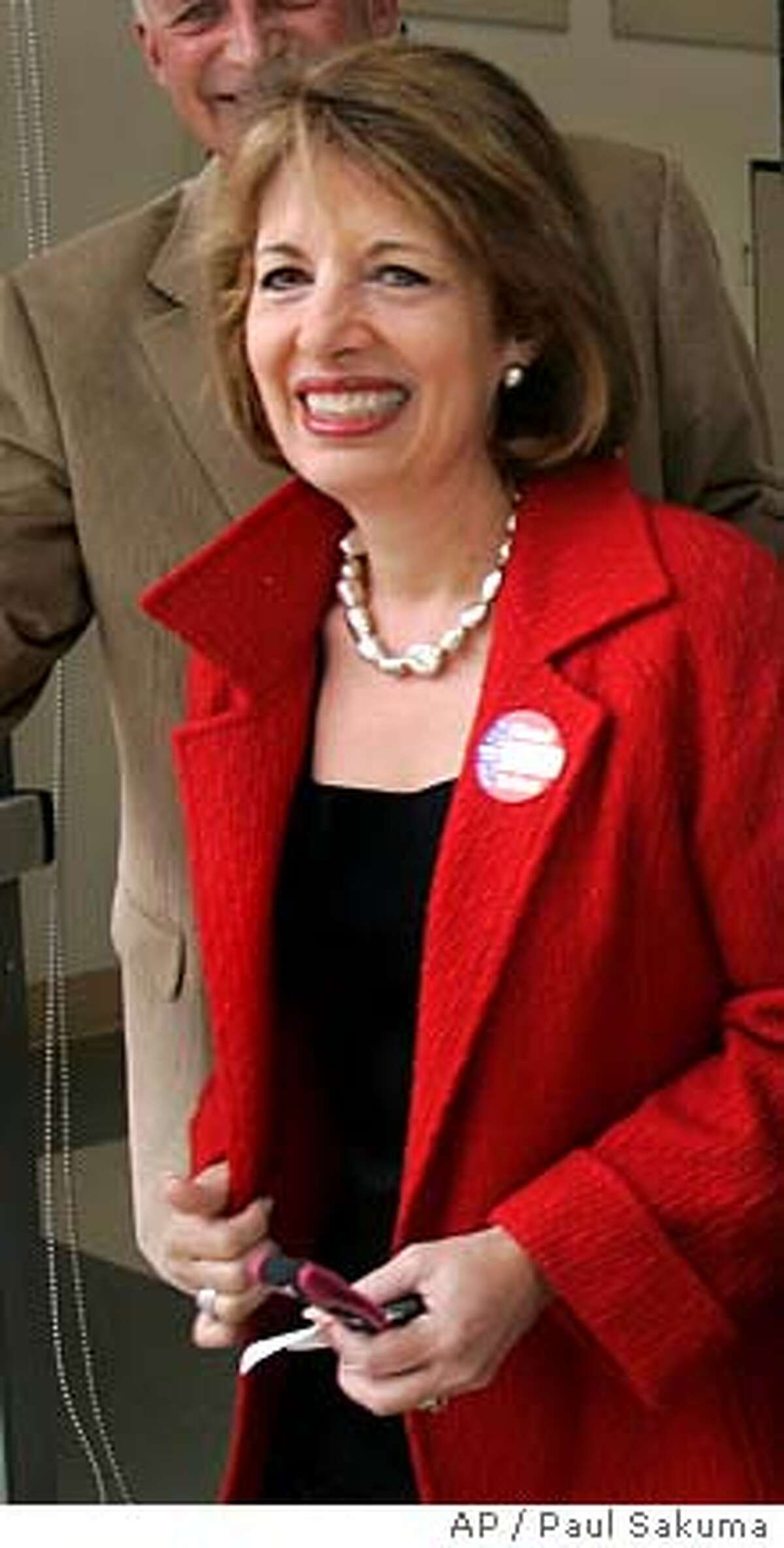 Jackie Speier, right, leaves with her husband, Barry Dennis, left, after voting in a special election in San Mateo, Calif., Tuesday, April 8, 2008. Speier, who as a congressional aide nearly 30 years ago was shot and left for dead on a Guyana airstrip, is seeking to win the House seat once held by her former boss. A former California state lawmaker, Speier was the favorite to win a special election to fill the House seat left vacant by the death of Democratic Rep. Tom Lantos. (AP Photo/Paul Sakuma)