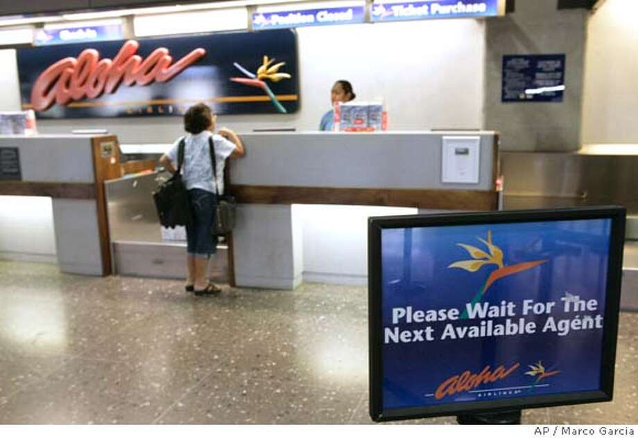** FILE ** A passenger checks in at the Aloha Airlines counter at the Honolulu International Airport in Honolulu in this Sunday, March 30, 2008 file photo. Aloha Airlines, ATA, Skybus _ one week, three airlines out of business. Add in soon-to-be-defunct Champion Air and December casualty MAXjet Airways, and last week's rapid-fire round of airline failures starts to look like an ominous trend. (AP Photo/Marco Garcia)  Ran on: 04-10-2008  The Aloha Airlines ticket counter in Honolulu on the day the carrier announced it would stop service. Photo: Marco Garcia