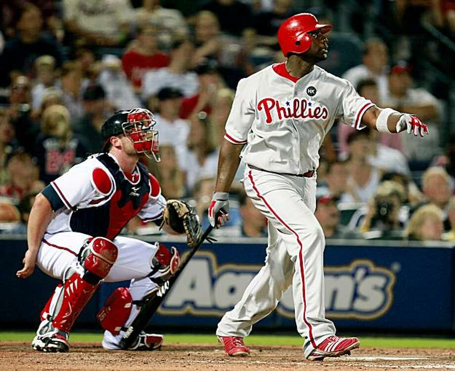 Philadelphia Phillies' Ryan Howard, right, breaks a 2-2 tie with a solo home run as Atlanta Braves catcher Brian McCann, left, looks on in the ninth inning of a baseball game in Atlanta, Friday, Aug. 14, 2009. (AP Photo/John Bazemore) Photo: John Bazemore, AP