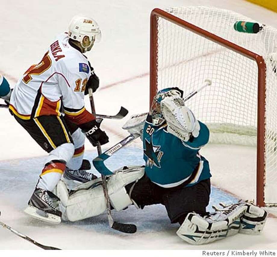 Calgary Flames Jarome Iginla (L) sneaks the puck past San Jose Sharks goaltender Evgeni Nabokov for a goal in the second period of the first round NHL hockey playoff game in San Jose, California, April 9, 2008. REUTERS/Kimberly White (UNITED STATES)  Ran on: 04-10-2008  Jarome Iginla runs into Sharks' goalie Evgeni Nabokov on a shot that bounced back to Stephane Yelle, who flipped it in to give the Flames their third goal, which proved to be the decider. Photo: KIMBERLY WHITE