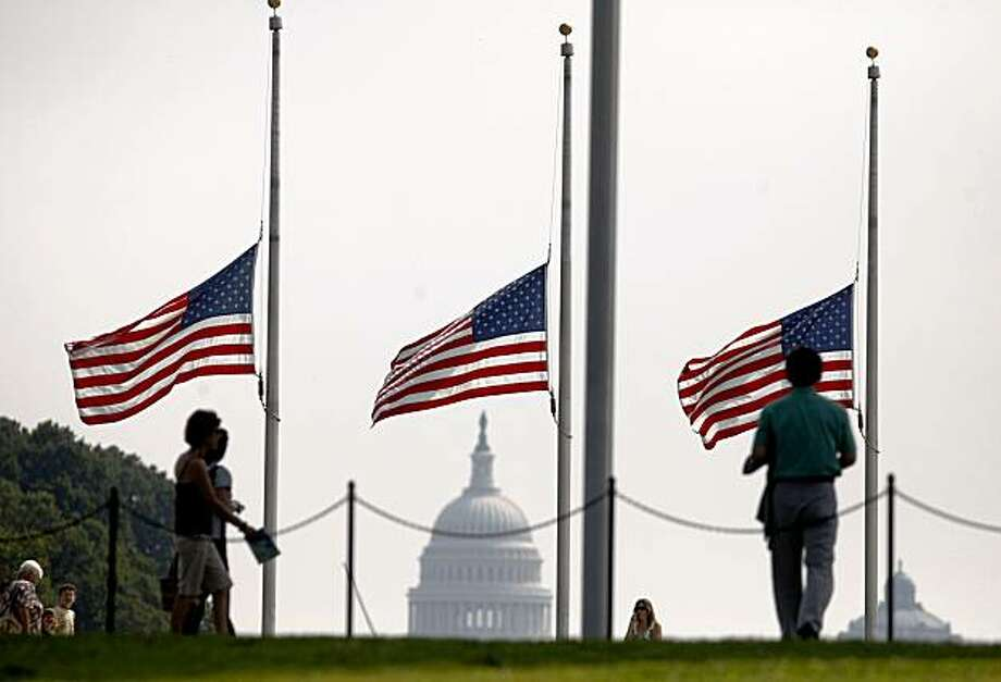 The U.S. Capitol is seen in the background as flags fly at half-staff at the Washington Monument in Washington, Wednesday, Aug. 26, 2009, in honor of the passing of Sen. Edward Kennedy, D-Mass. (AP Photo/Gerald Herbert) Photo: Gerald Herbert, AP