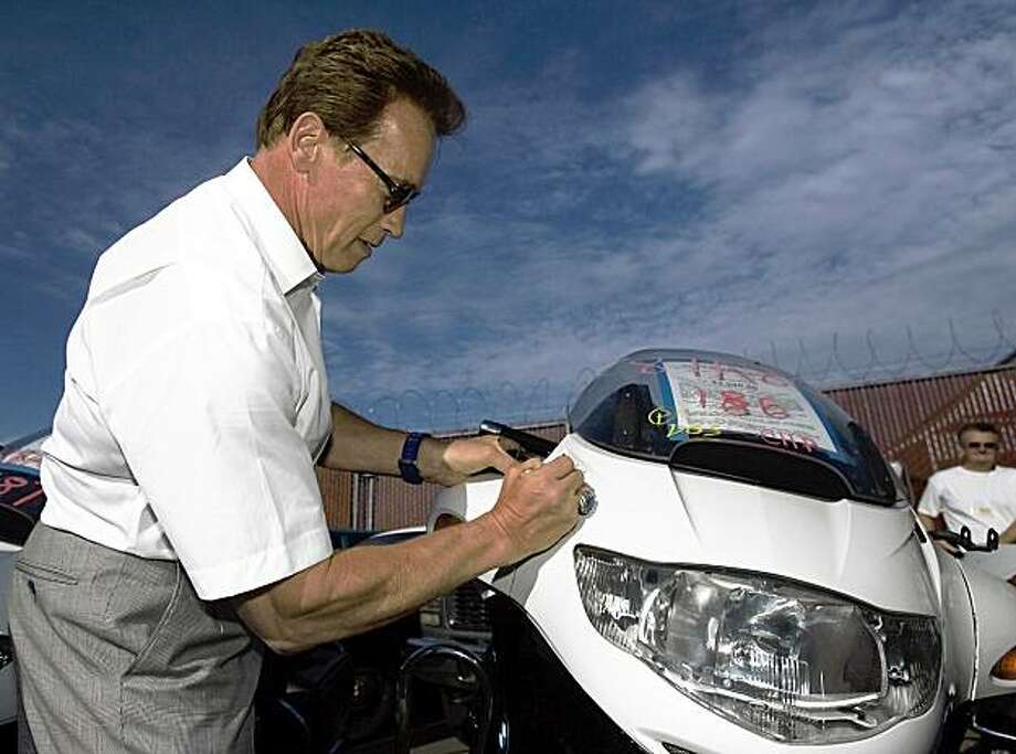 SACRAMENTO, CA - AUGUST 28:   Governor Arnold Schwarzenegger autographs a state-surplus BMW motorcycle set for auction as part of The Great California Garage Sale August 28, 2009, in Sacramento, California. The sale includes more than 5000 surplus state-owned items. Some customers waited in line for more than 12 hours to be one of the first at the sale which was ordered by the Governor. Photo by Robert Durell/Getty Images) Photo: Robert Durell, Getty Images