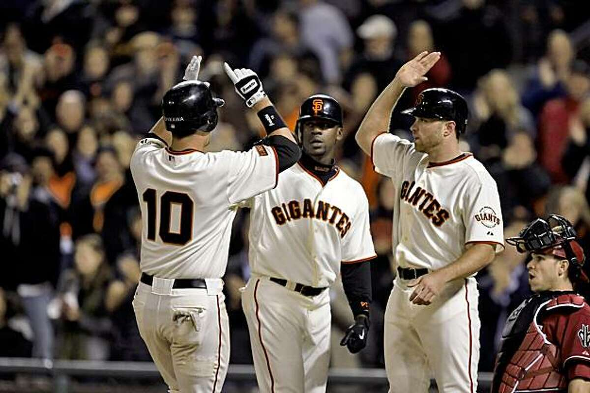 Travis Ishikawa is greeted at home by teammates Fred Lewis and Nate Schierholtz after hitting his eighth inning three-run homerun. The San Francisco Giants played the Arizona Diamondbacks at AT&T Park in San Francisco, Calif., on Tuesday, August 25, 2009. The Giants won the game, 5-4.
