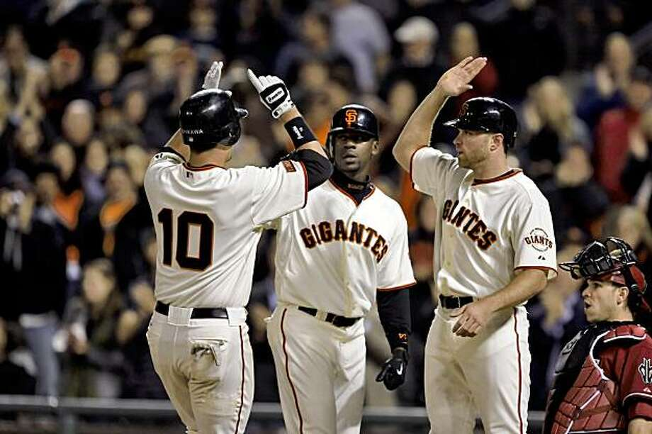 Travis Ishikawa is greeted at home by teammates Fred Lewis and Nate Schierholtz after hitting his eighth inning three-run homerun. The San Francisco Giants played the Arizona Diamondbacks at AT&T Park in San Francisco, Calif., on Tuesday, August 25, 2009. The Giants won the game, 5-4. Photo: Carlos Avila Gonzalez, The Chronicle