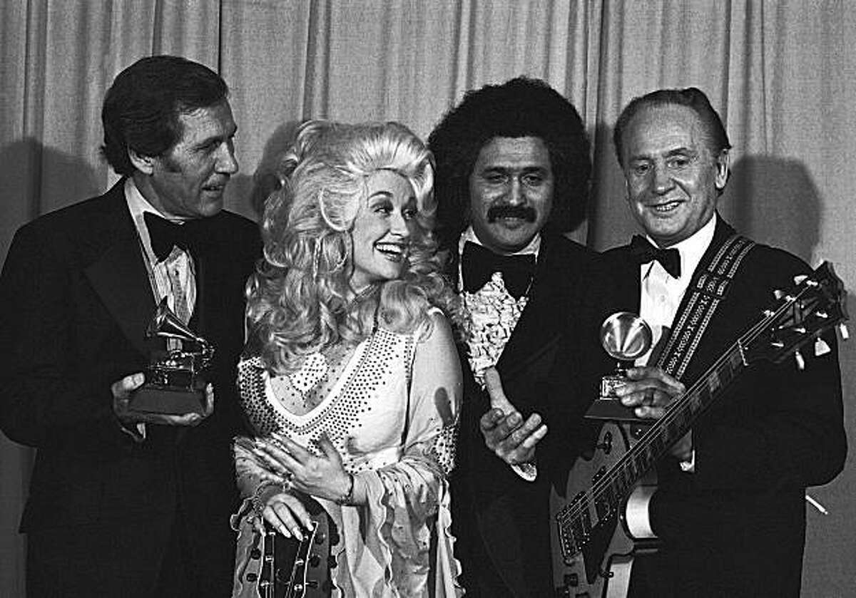 FILE - In this Feb. 19, 1977 file photo, Les Paul, right, and Chet Atkins, left, are presented Grammies by Dolly Parton and Freddie Fender, second from right, at 19th annual Grammy Awards in Los Angeles. Paul, 94, the guitarist and inventor who changed the course of music with the electric guitar and multitrack recording and had a string of hits, died, Thursday, Aug. 13, 2009 in White Plains, N.Y., according to Gibson Guitar. (AP Photo/George Brich, file)