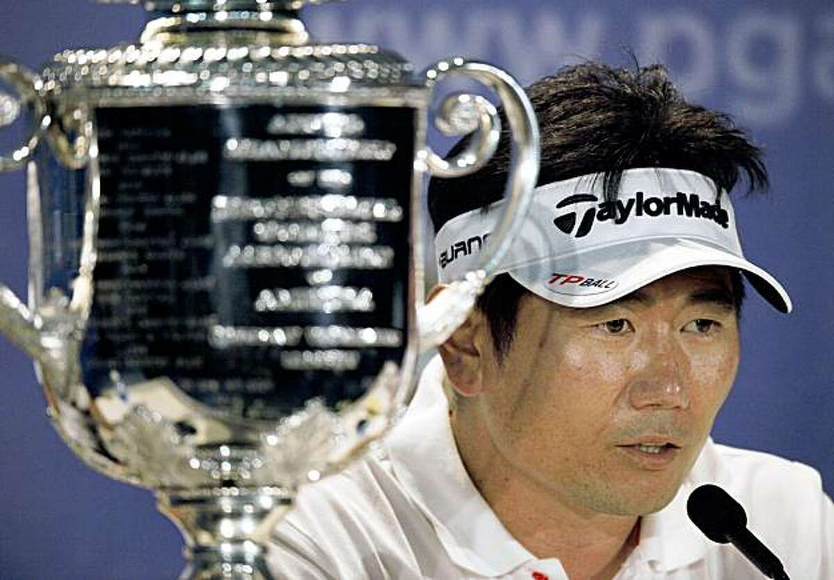 Y.E. Yang, of South Korea, sitting next to Wanamaker Trophy, answers questions during a press conference after winning the 91st PGA Championship at the Hazeltine National Golf Club in Chaska, Minn., Sunday, Aug. 16, 2009. (AP Photo/Charlie Riedel)