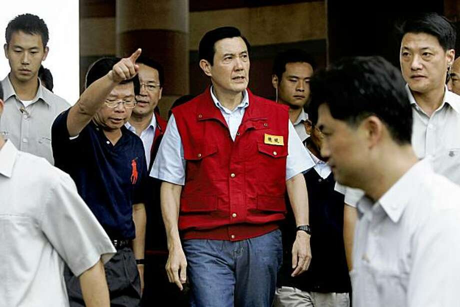 Taiwan's President Ma Ying-jeou, center, arrives at the emergency landing zone for rescued villagers that were trapped by Typhoon Morakot in Cishan, Taiwan, Wednesday, Aug. 12, 2009. Police said Wednesday that there is no way to know for sure how many people remain buried in the catastrophic mudslide that struck a remote mountain village in Taiwan over the weekend when a typhoon lashed the region. (AP Photo/Wally Santana) Photo: Wally Santana, AP