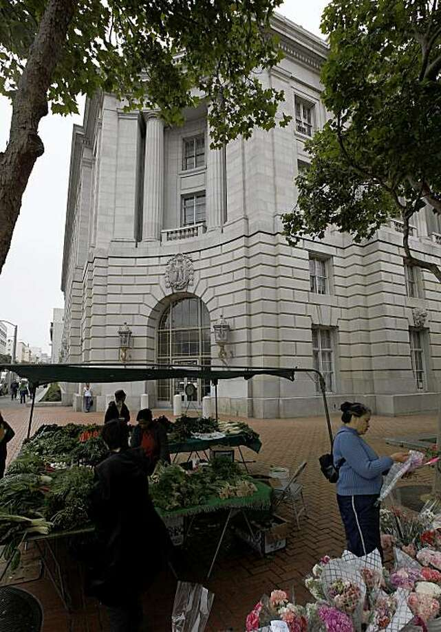 People shop the  weekly farmers market, on Wednesday May 6, 2009, in front of 50 United Nations Plaza, the long abandoned Federal building in the heart of San Francisco, Calif., which will be refurbished and made seismically safe with an infusion of stimulus funds. Photo: Michael Macor, The Chronicle