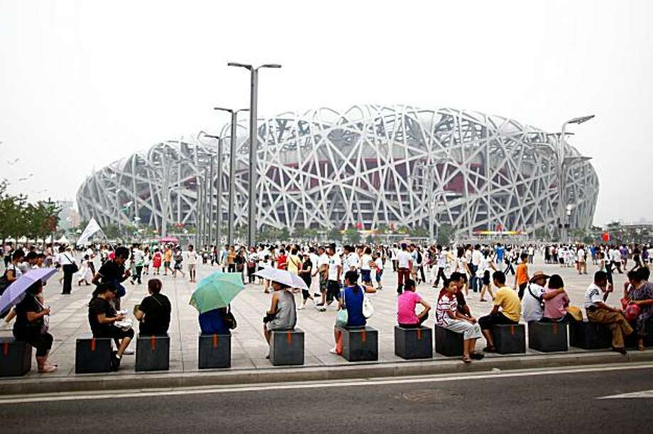 BEIJING - AUGUST 04:  Tourists rest outside the National Olympic Stadium, known as Bird's Nest on August 4, 2009 in Beijing, China. The Olympic Green has already become the most popular scenic spot of Beijing in the past year. China will hold various activities to mark one year anniversary of the Beijing Olympic Games.  (Photo by Feng Li/Getty Images) Photo: Feng Li, Getty Images
