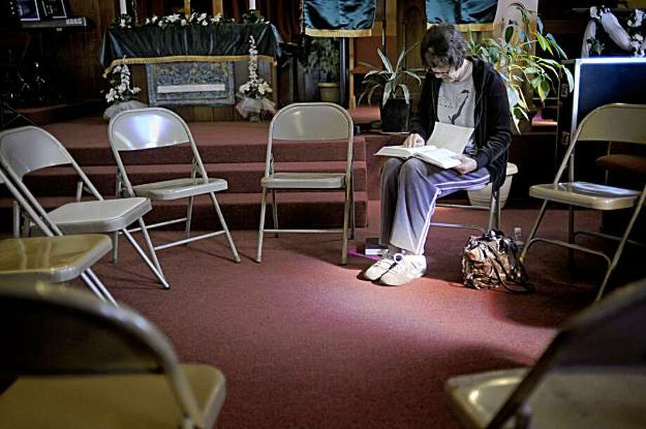 Gaile Patton reads the bible and prays at the United Methodist Church East Salinas Family Center in Salinas, Calif. Friday, Aug. 14, 2009. Church leaders are hoping 24-7 prayer vigils would help put an end to the recent spike in gang violence gripping this Central California farming community that's left seven dead in three weeks. Gang activity has long plagued the region, but the latest outbreak has spotlighted a city under siege. In 2008, Salinas had 23 gang-related killings contributing to its record 25 homicides. (AP Photo/Russel A. Daniels) Photo: Russel A. Daniels, AP
