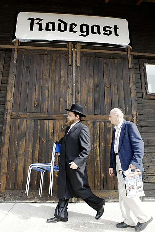 Symcha Keller, a Lodz Jewish community leader, left, carries chairs at Memorial Radegast train station in Lodz during a remembrance ceremony marking the 65th anniversary of the last transports from the Lodz ghetto to death camps, in Lodz, Poland, on Thursday Aug. 27, 2009. (AP Photo/Czarek Sokolowski) Photo: Czarek Sokolowski, AP