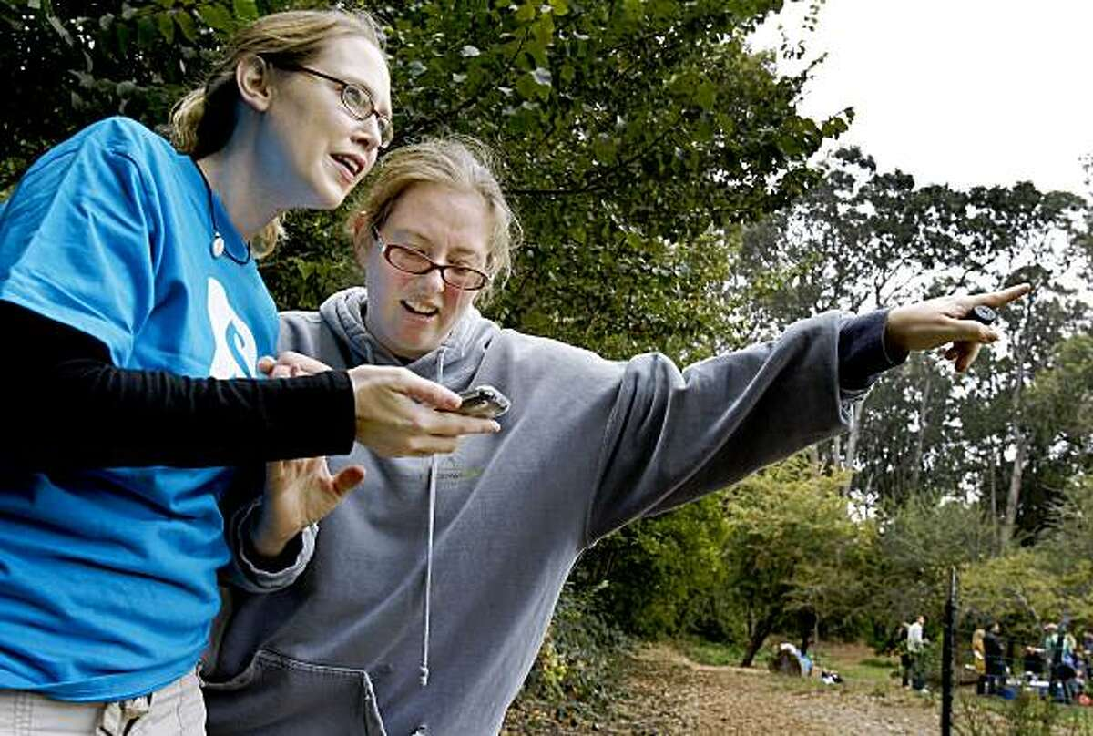 """Stephanie Raney (left) gets some help with Seek n' Spell from Brandy Wiegers at the picnic for enthusiasts. Zach Saul is a designer of a new iPhone application called Seek n' Spell which was awarded """"best use of technology"""" at New York's Come Out and Play festival. Many gathered in Golden Gate Park Sunday August 23, 2009 to play the new game."""