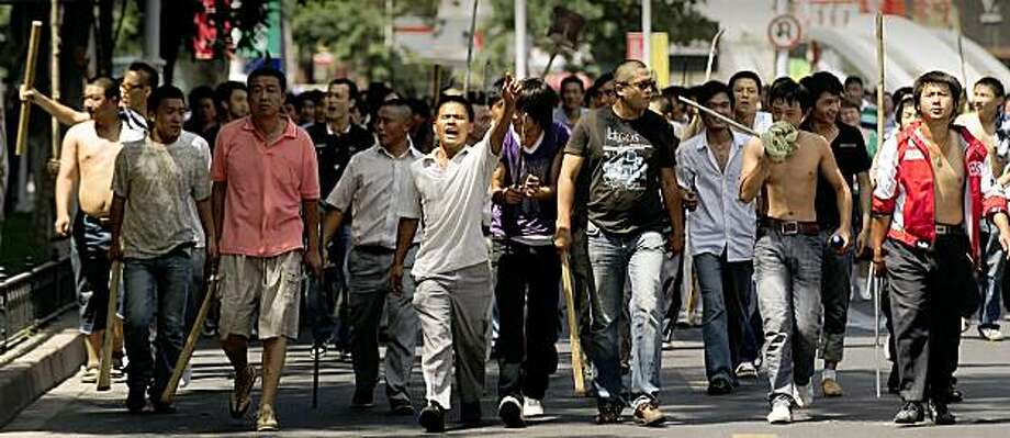 TO GO WITH STORY China-unrest-Xinjiang-trial (FILES) In a file picture taken on July 7, 2009, a large group of Han Chinese walk up a street carrying sticks and shovels in Urumqi in China's far west Xinjiang province. China is expected to put more than 200 people on trial this week for alleged involvement in deadly unrest in the country's northwest Muslim-majority region of Xinjiang, state media said on August 24, 2009. AFP PHOTO/Peter PARKS (Photo credit should read PETER PARKS/AFP/Getty Images) Photo: Peter Parks, AFP/Getty Images