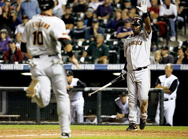 San Francisco Giants' Edgar Renteria, back, celebrates as teammate Travis Ishikawa, left front, also scores on a triple by Eugenio Velez against the Colorado Rockies in the 14th inning of a baseball game in Denver on Monday, Aug. 24, 2009. (AP Photo/David Zalubowski) Photo: David Zalubowski, AP