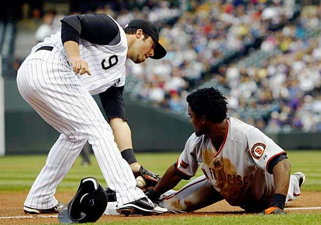 Colorado Rockies third baseman Ian Stewart, left, turns to apply a late tag as San Francisco Giants' Eugenio Velez advances from second base to third on a sacrifice fly in the first inning of a baseball game in Denver on Monday, Aug. 24, 2009. (AP Photo/David Zalubowski) Photo: David Zalubowski, AP