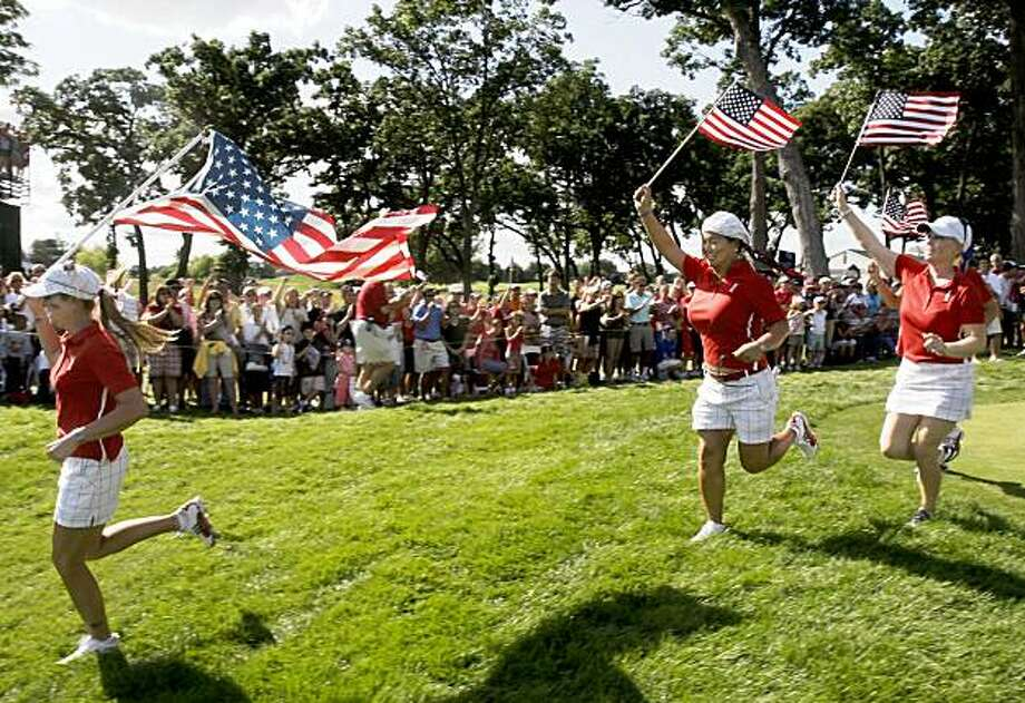 Team USA's Paula Creamer, left to right, Christina Kim and Morgan Pressel run on the 18th hole after their singles match at the Solheim Cup golf tournament Sunday, Aug. 23, 2009, at Rich Harvest Farms in Sugar Grove, Ill. The USA team won 16-12 to retain the cup. (AP Photo/Michael Conroy) Photo: Michael Conroy, AP