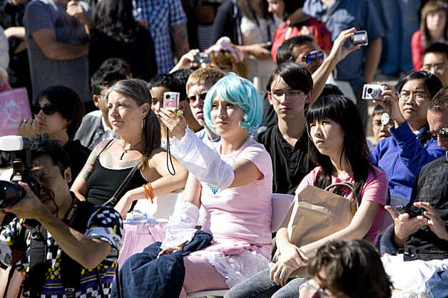 Maria Watanabe (center) snaps a photo while watching the performances at the J-Pop Summit Festival in Japantown in San Francisco on Saturday. Photo: Laura Morton, Special To The Chronicle