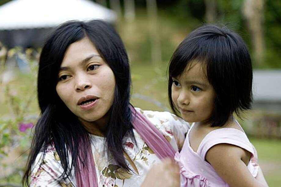 Muslim model Kartika Sari Dewi Shukarno, 32, who will be caned for drinking alcohol, is pictured with her daughter Wan Kaitlynn Sari Dewi, 5 at her father's home in Karai, north of Kuala Lumpur on August 24, 2009.  The Muslim model who is to be caned for drinking alcohol said she is planning a pilgrimage to Mecca, and seeking solace in prayer as she prepares to face her punishment this week. Shukarno will be the first woman to be caned under Islamic law in Malaysia, a moderate Muslim-majority country where the landmark case has caused a national sensation.  TOPSHOTS  AFP PHOTO / KAMARUL AKHIR (Photo credit should read KAMARUL AKHIR/AFP/Getty Images) Photo: Kamarul Akhir, AFP/Getty Images