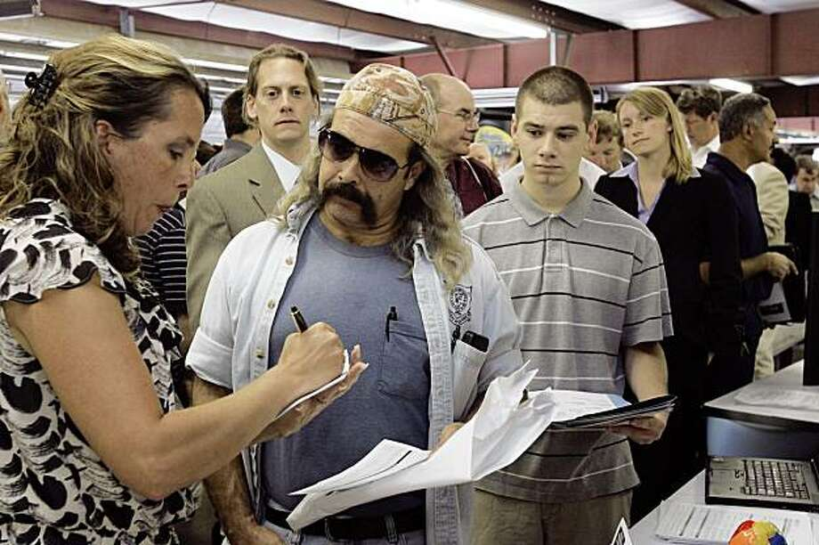 Steve Costa of Barnstead, N.H., second from left, interviews for a job at GT Solar, during a job fair at New Hampshire Motor Speedway, host to NASCAR races  in Loudon, N.H., Thursday, Aug. 27, 2009.(AP Photo/Jim Cole) Photo: Jim Cole, AP
