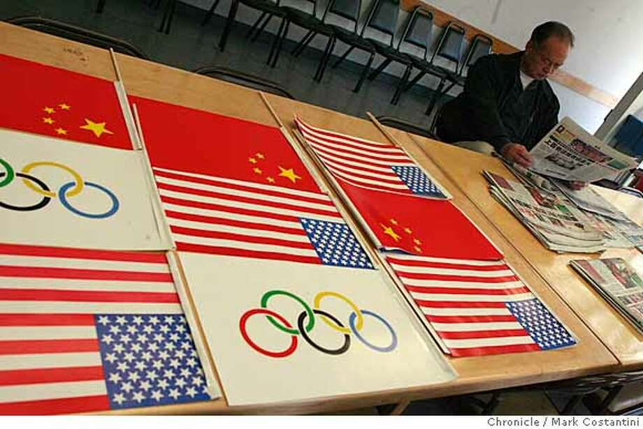 Sik Hoi Wong reads a newspaper as Chinese, American and Olympic flags lay on a table at the Chinese American Association of Commerce on Clay St. in the Chinatown district of San Francisco, Calif. on April 3 ,2008. Photo by Mark Costantini / San Francisco Chronicle.  Ran on: 04-06-2008  Chinese, American and Olympic flags show pride at the Chinese American Association of Commerce. Photo: Mark Costantini