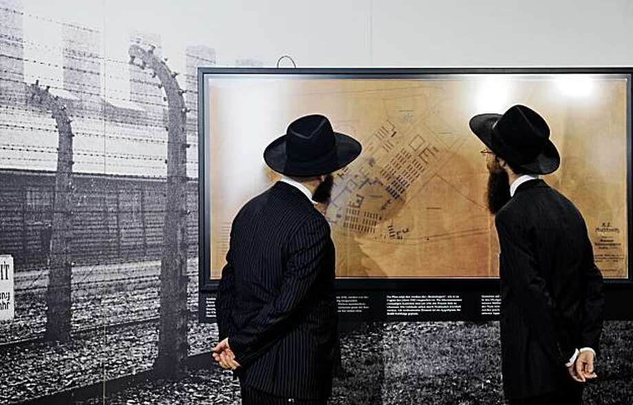 Rabbi Yehuda Teichtal, left, and Shmuel Segal look at an architectural plan of the Auschwitz death camp in Berlin on Thursday Aug. 27, 2009. Plans and blueprints that were discovered in Berlin last year were handed over Thursday to Israeli Prime Minister Benjamin Netanyahu for display at Israel's Holocaust memorial. (AP Photo/Rainer Jensen, Pool) Photo: Rainer Jensen, AP