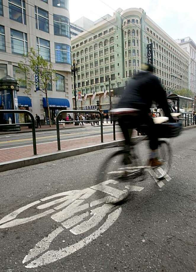 A bicyclist pedals down a designated bike lane at Fourth and Market streets in downtown San Francisco. Photo: Paul Chinn, SFC
