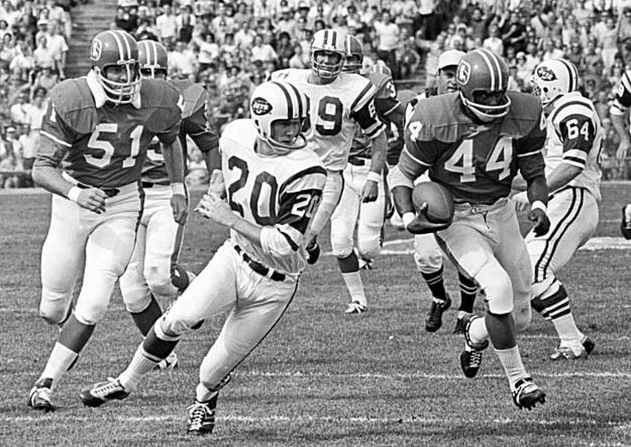 In this Sept. 22, 1969 file photo, Denver Broncos running back Floyd Little (4) runs past New York Jets defender Steve O'Neal (2) during a football game in Denver. Little and former star defensive back Dick LeBeau are finalists for the Pro Football Hall of Fame, it was announced on Tuesday, Aug. 25, 2009. (AP Photo/File) Photo: AP