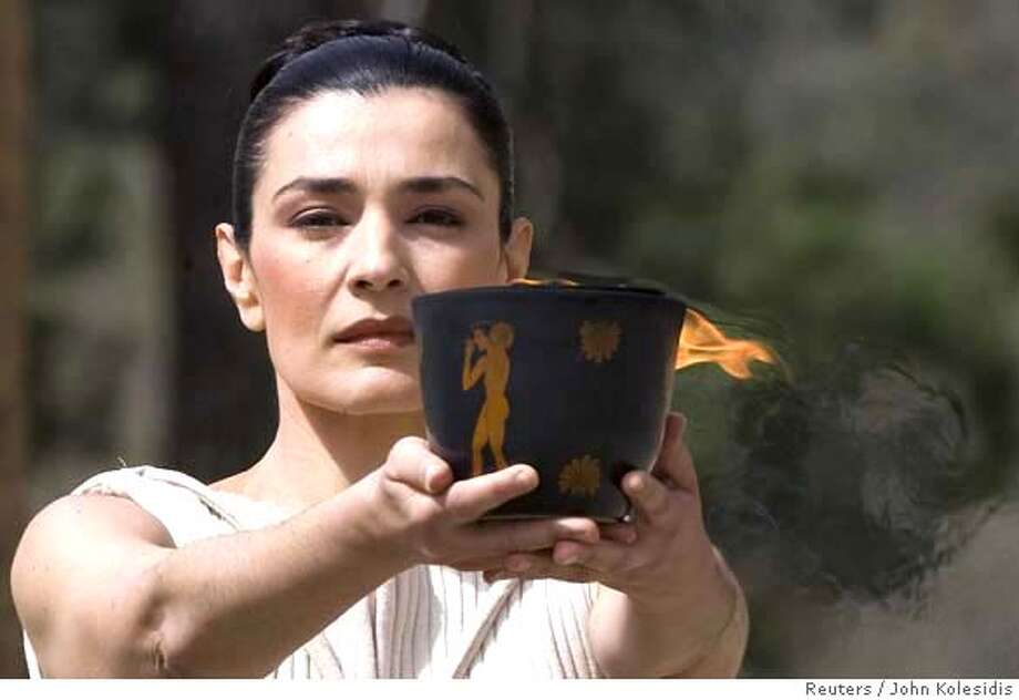 ###Live Caption:The Olympic flame is carried to the torch lighting ceremony by Greek actress Maria Nafpliotou, playing the role of High Priestess, at the site of ancient Olympia in Greece, March 24, 2008. REUTERS/John Kolesidis (GREECE)###Caption History:The Olympic flame is carried to the torch lighting ceremony by Greek actress Maria Nafpliotou, playing the role of High Priestess, at the site of ancient Olympia in Greece, March 24, 2008. REUTERS/John Kolesidis (GREECE)###Notes:The Olympic flame is carried to torch lighting ceremony for the Beijing 2008 Games at the site of Olympia in Greece###Special Instructions: Photo: JOHN KOLESIDIS