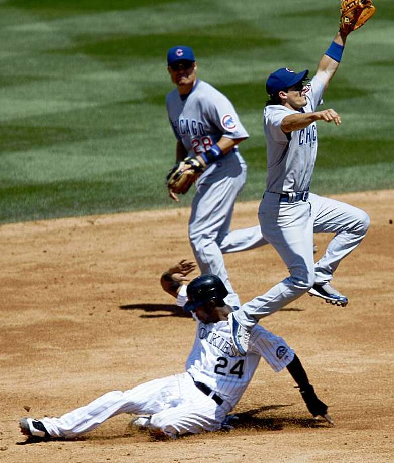 Colorado Rockies' Dexter Fowler, front left, steals second base as Chicago Cubs shortstop Ryan Theriot, front right, fields the throw while second baseman Jeff Baker, back, comes in to cover in the third inning of the Rockies' 11-5 victory in a baseball game in Denver on Sunday, Aug. 9, 2009. (AP Photo/David Zalubowski) Photo: David Zalubowski, AP