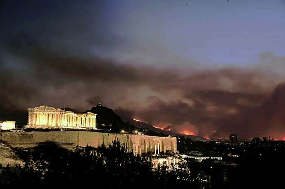 ATHENS, GREECE - AUGUST 23:  Wild fire and smoke illuminate the sky behind the ancient Acropolis on August 23, in Athens, Greece. Authorities have declared a state of emergency as the large wildfire has raged since Friday, destroying homes and forcing thousands to flee the inferno. The blaze is the worst suffered by mainland Greece since 2007.  (Photo by Milos Bicanski/Getty Images) Photo: Milos Bicanski, Getty Images