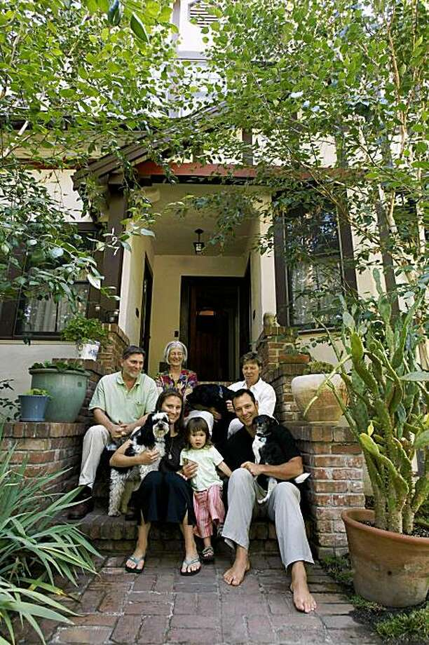 Ben Ladomirak, bottom right, sits with his family, daughter Lleu (cq) , 2, left, wife, Jesse, far left bottom, Jesse's parents, Bob Fletcher, left, and Marguerite Fletcher, above Jesse, and Ben's mother, Sylvia Seibert, top right, along with dogs, Checker in Jesse's arms, Mason in Ben's arms and Diva in Sylvia's arms, on the stairs outside their three unit Palo Alto property Friday morning, July 17, 2009. Photo: Erin Lubin, Special To The Chronicle