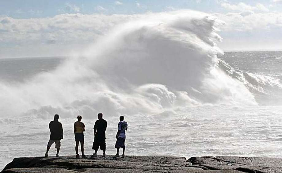 Wave watchers check out the ocean action near Peggy's Cove, N.S. Sunday, Aug. 23, 2009. Hurricane Bill brought a steady downpour and fierce winds to Nova Scotia, knocking out power, canceling flights and drawing curious onlookers hoping to catch a glimpse of crashing waves as it marched through Atlantic Canada on Sunday. (AP Photo/Tim Krochak, The Canadian Press) Photo: Tim Krochak, AP